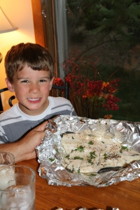 Austin excited to see his freshly caught trout seasoned and grilled for dinner!